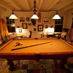 Game Room Image with Betsy Ross flag, pool table, white painted walls, nice looking furnitures and decors at night