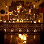 Main Bar Image with dimly lit lounge, scented candles in glass, bar stools and wide variety of liquor displayed