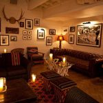 Main Bar Image with dimly lit lounge, comfy couches, scented candles in glass, and nice wall frame designs and decors